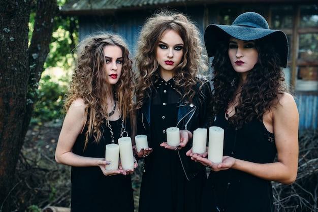 Drie vintage vrouwen als heksen, poseren en houden de kaarsen in hun handen aan de vooravond van halloween
