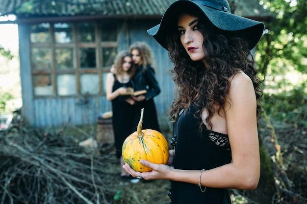 Drie vintage vrouwen als heksen poseren voor een verlaten gebouw aan de vooravond van halloween