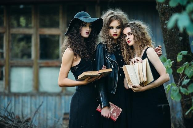 Drie vintage vrouwen als heksen poseren voor een verlaten gebouw met boeken in de hand aan de vooravond van halloween
