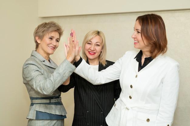 Drie volwassen vrouwen in pak houden elkaars hand vast op kantoor