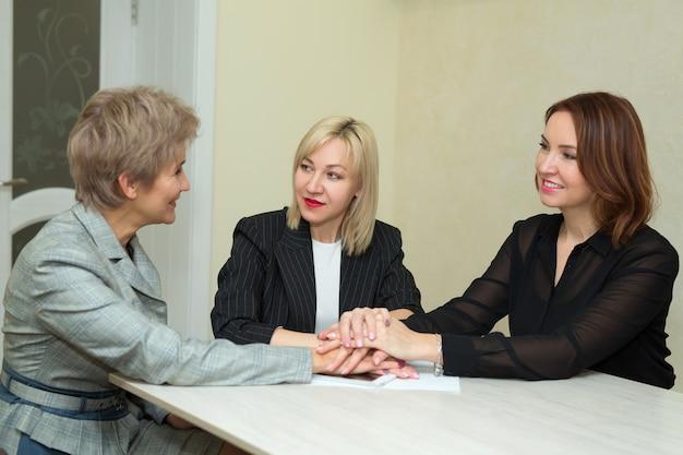 Drie volwassen vrouwen in pak praten aan de tafel in het kantoor, hand in hand