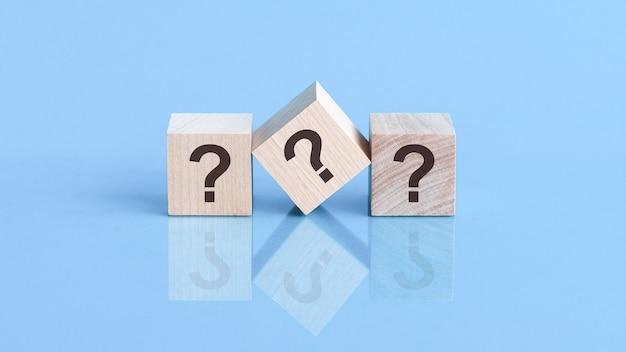 Drie vraagtekens geschreven op houten kubussen, liggend op de blauwe tafel, concept
