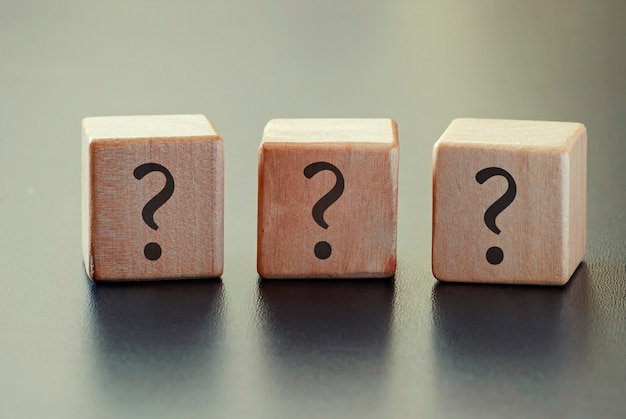 Drie vraagtekens op een rij van houten blokken