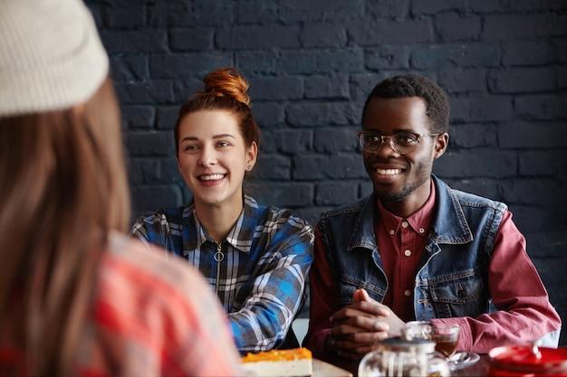 Drie vrienden brengen leuke tijd samen door, genieten van gemakkelijke, levendige gesprekken in het café, eten een dessert en drinken thee. mensen, levensstijl