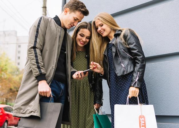 Drie vrienden die het winkelen zakken houden die smartphone bekijken