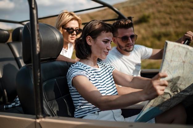 Drie vrienden die met de auto reizen en de kaart controleren