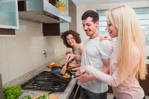 Drie vrienden die pret maken terwijl het koken van voedsel in de pan