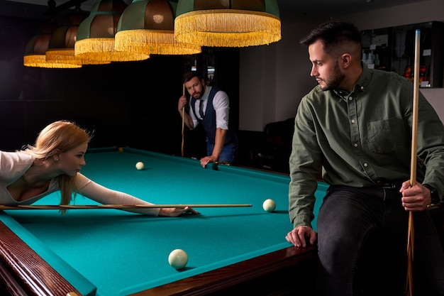 Drie vrienden die samen gezellig biljart, snooker of pool spelen, genieten van vrije tijd. plezier, biljart, vrije tijd, rustconcept