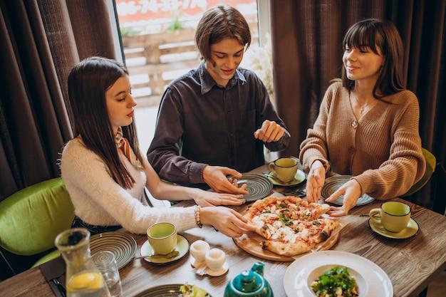 Drie vrienden die samen pizza eten in een café