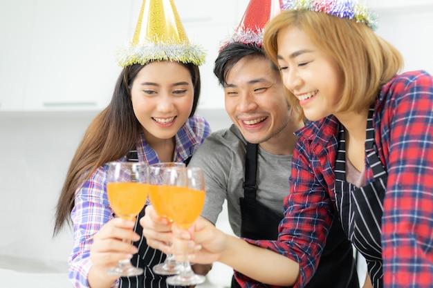Drie vrienden die van het glas van de partij genieten, die jus d'orangecocktail samen drinken