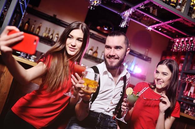 Drie vrienden, een jonge kerel en twee schattige meisjes die alcoholische cocktails houden, maken een selfie van een bar of een nachtclub