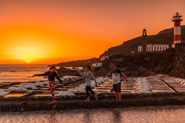 Drie vrienden in de oranje zonsondergang op de zoutvlakten en op de achtergrond de fuencaliente-vuurtoren op de route van de vulkanen ten zuiden van het eiland la palma, canarische eilanden, spanje