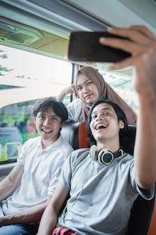Drie vrienden lachen en poseren voor de camera van hun mobiele telefoon terwijl ze samen selfies maken in de bus