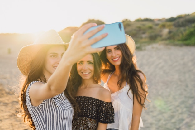 Drie vrienden nemen een selfie op het strand