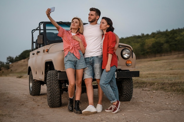 Drie vrienden nemen selfie met smartphone terwijl ze met de auto reizen