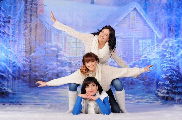Drie vrienden of zussen hebben samen plezier voor kerstmis.