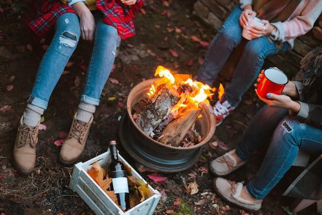 Drie vrienden ontspannen comfortabel en drinken wijn op een herfstavond in de open lucht bij het vuur in de achtertuin