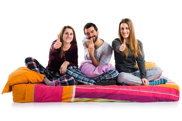 Drie vrienden op een bed met duim omhoog