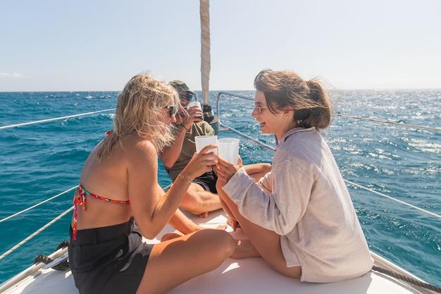 Drie vrienden op een boot tijdens een feestje lachen en hebben plezier het is zomer ze genieten van een drankje
