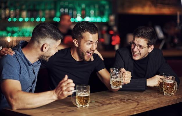 Drie vrienden rusten in de kroeg met bier in handen
