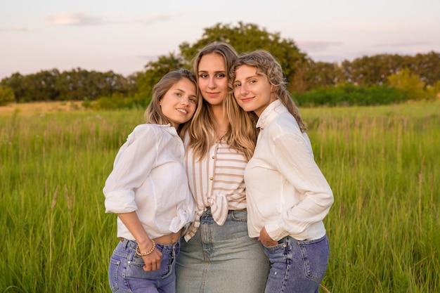 Drie vrienden rusten uit in de natuur. ze glimlachen en maken foto's