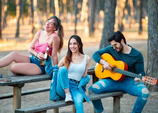 Drie vrienden spelen gitaar en hebben plezier buitenshuis, meisje in focus center