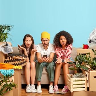 Drie vrienden van gemengd ras poseren samen op een comfortabele bank, hebben verbaasde uitdrukkingen gefrustreerd, surfen op internet op hun mobiele telefoon, kunnen geen passend interieur vinden voor een nieuwe verhuizing in een gekocht appartement
