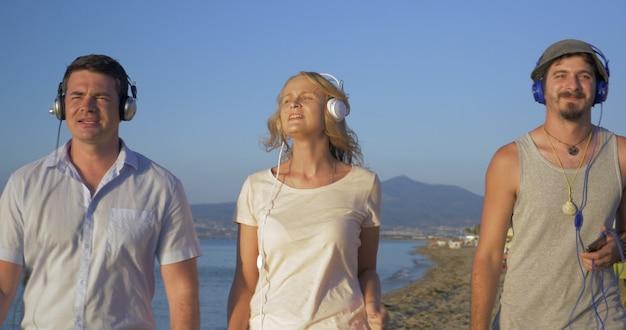 Drie vrienden wandelen met muziek op het strand