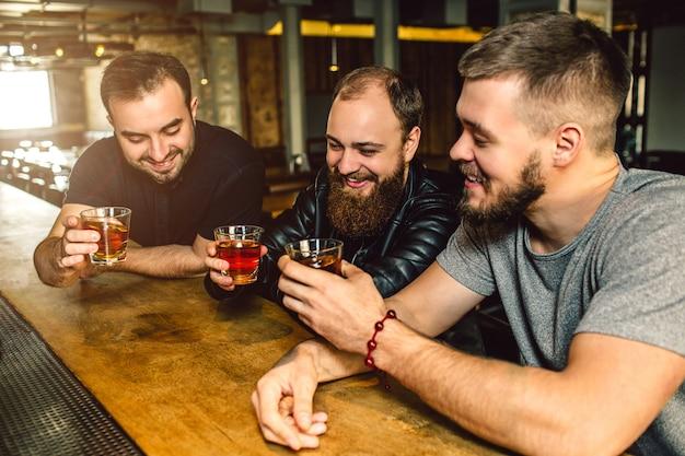 Drie vrienden zitten samen bij toog. ze houden glazen alcohol in handen. mannen glimlachen.