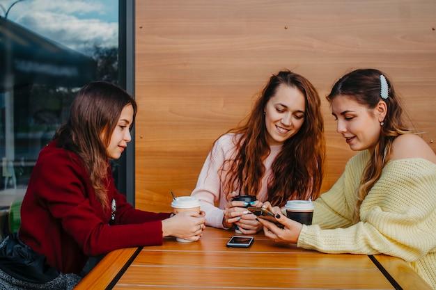 Drie vriendinnen chatten in een café voor een kopje koffie