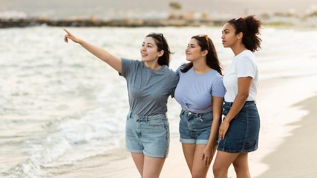 Drie vriendinnen die het uitzicht op het strand bewonderen
