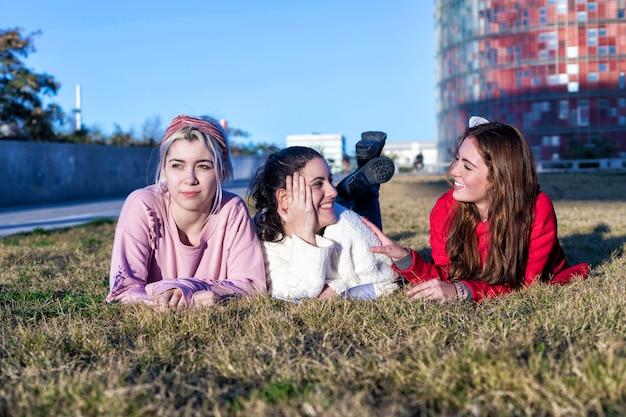 Drie vriendinnen die op het gras in een park in de herfst liggen