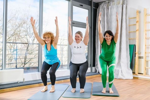 Drie vriendinnen oefenen samen yoga pilates fitness, groepstraining, squats met handen omhoog