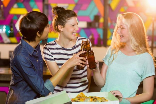 Drie vriendinnen roosteren flesje bier