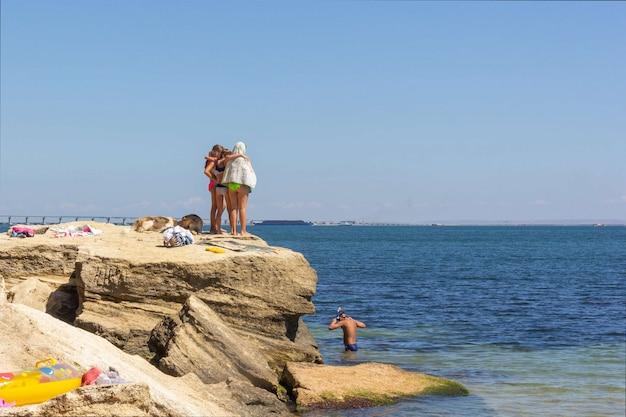 Drie vriendinnen staan elkaar omhelzend aan de kust en kijken naar een jongen die duikt met een onderwatermasker
