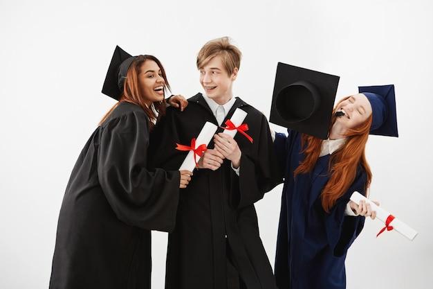 Drie vrolijke afgestudeerde klasgenoten vieren lachend blij. toekomstige advocaten of medici, onderwijsconcept.