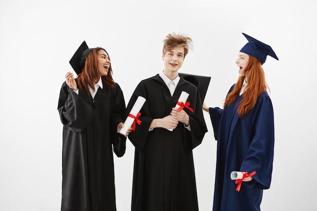 Drie vrolijke afgestudeerden glimlachen spreken gek houden met diploma's