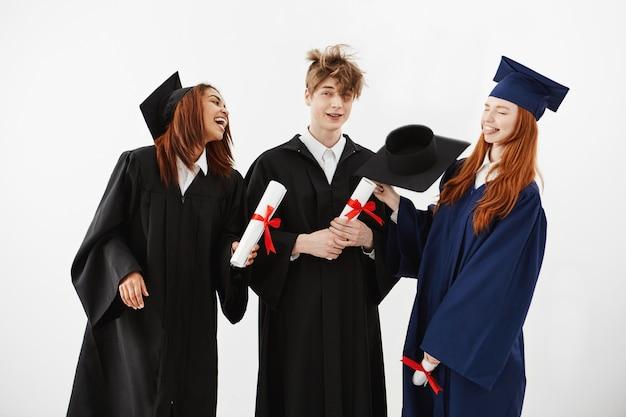 Drie vrolijke afgestudeerden lachend spreken voor de gek houden diploma's pesten en plezier maken