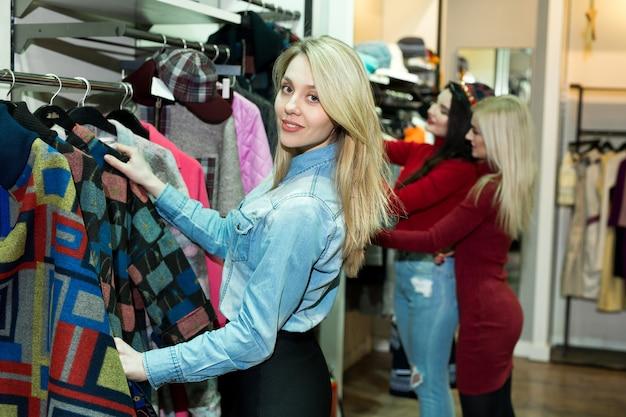 Drie vrolijke jonge vrouwen die warme jassen winkelen bij de kledingwinkel.