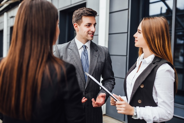 Drie vrolijke jonge zakenmensen die met elkaar praten terwijl ze buiten wandelen
