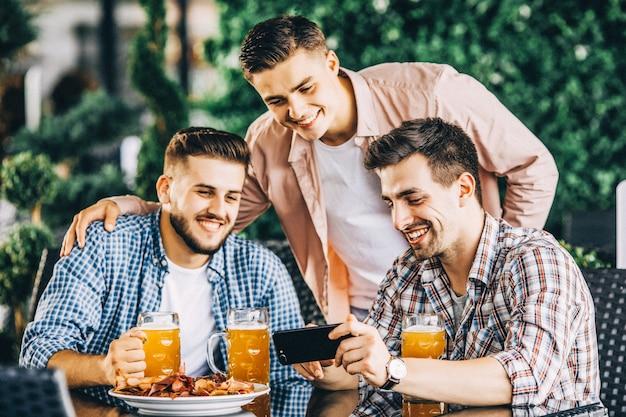 Drie vrolijke jongens zitten en zoeken iets aan de telefoon