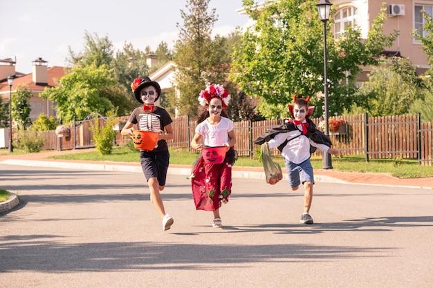 Drie vrolijke kinderen in halloween-kostuums die containers met zoete lekkernijen vasthouden terwijl ze op een zonnige herfstdag over de brede weg rennen