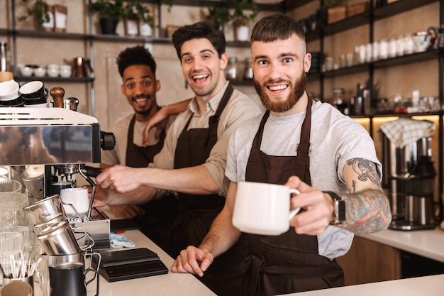 Drie vrolijke mannelijke barista's die binnenshuis aan de balie van de coffeeshop staan