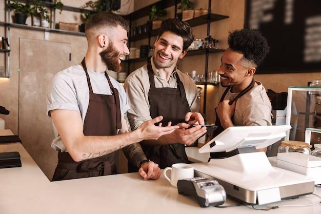 Drie vrolijke mannen barista's staan achter de toonbank in de coffeeshop, met behulp van mobiele telefoon