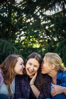 Drie vrolijke meisjes fluisteren en roddelen tegen groen gebladerte in het park.