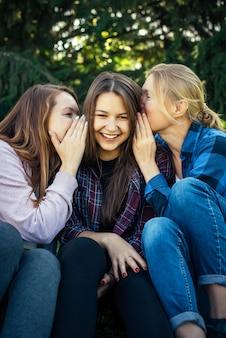 Drie vrolijke meisjes fluisteren en roddelen tegen groen gebladerte in park