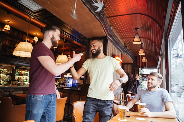 Drie vrolijke vrienden ontmoeten elkaar in biercafé