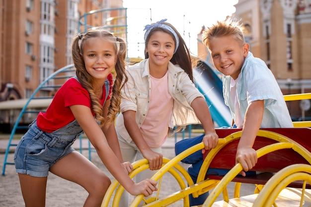 Drie vrolijke vrienden spelen in een speeltuin