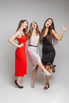 Drie vrolijke vriendinnen in prachtige jurken, geïsoleerd op een witte muur