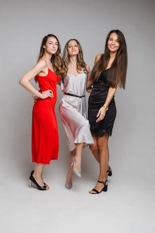 Drie vrolijke vriendinnen in prachtige jurken, op wit
